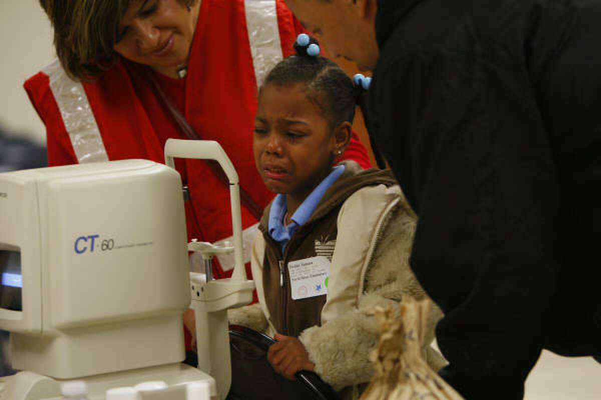 A staff member comforts Fielder Samara, 7, of North Shore Elementary, as she cries while having her vision checked at the Fifth Ward Multi-Service Center. The kids will receive comprehensive eye exams that tests for disease, color blindness, depth perception, eye muscle balance and the need for eyewear prescription.