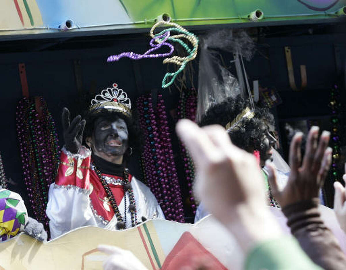 A member of the Zulu Social Aid and Pleasure Club tosses beads to revelers during Mardi Gras in New Orleans