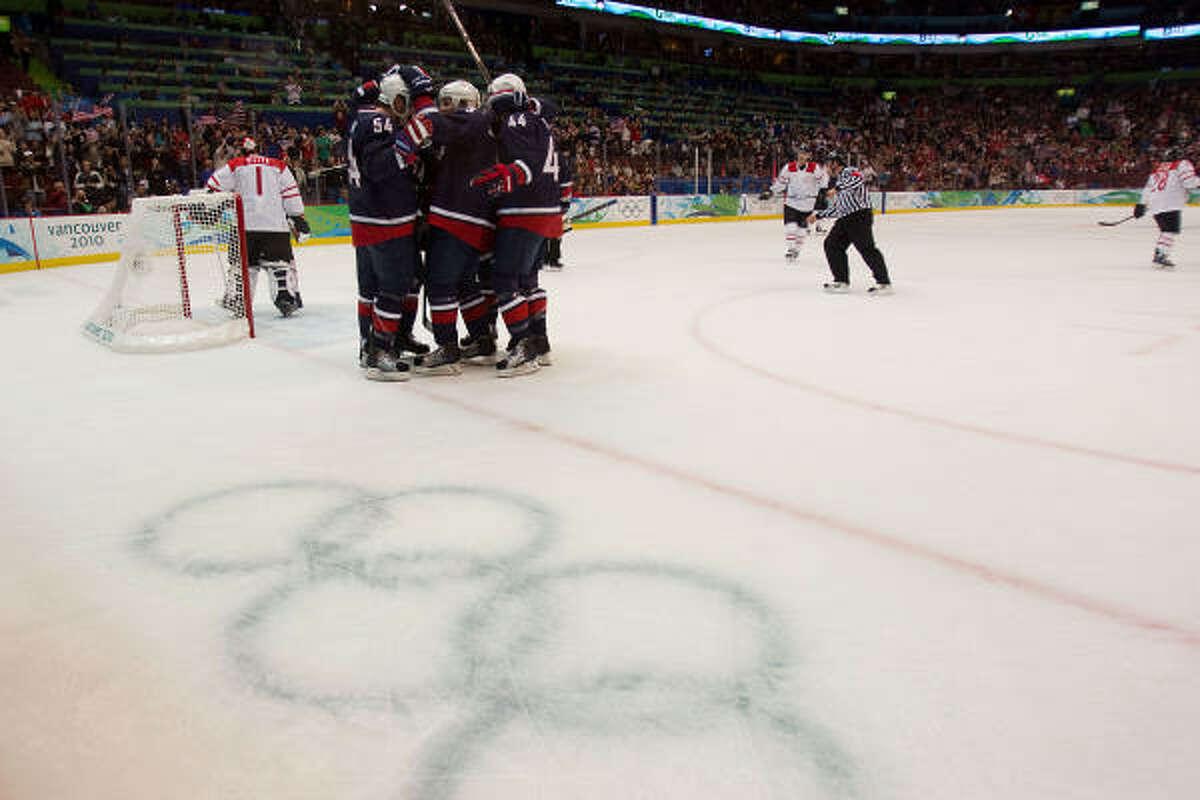 Team USA players celebrate around Bobby Ryan (54) after he scored past Switzerland goalie Jonas Hiller.