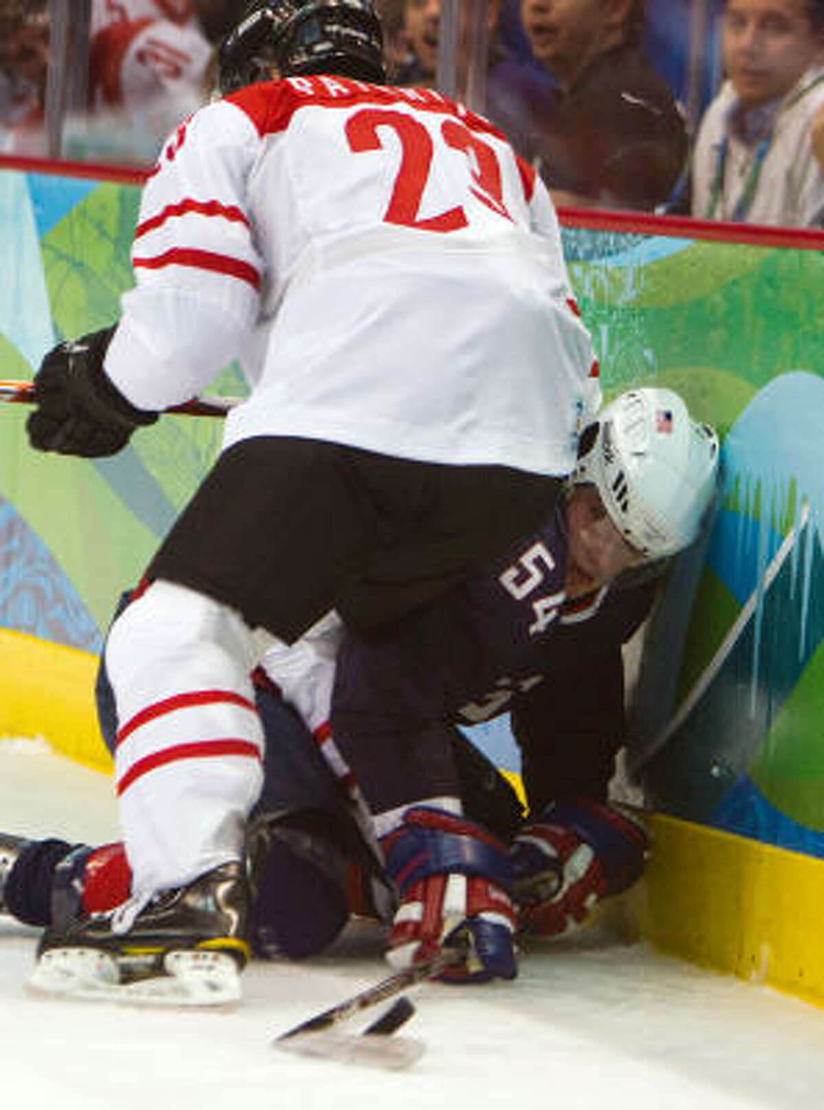 USA's Bobby Ryan mixes it up along the boards with Switzerland's Thierry Paterlini.