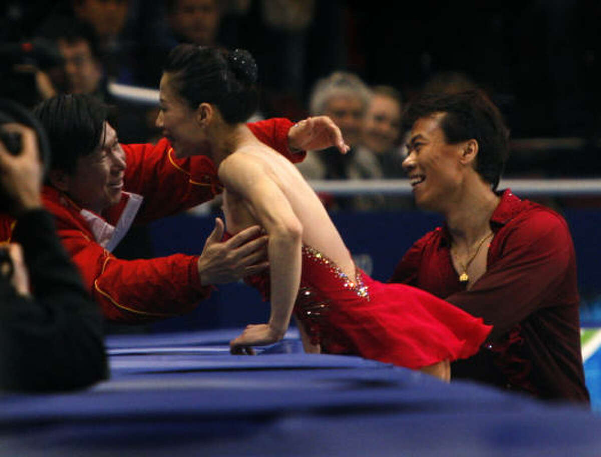 A Chinese coach hugs Xue Shen after Shen and Hongbo Zhao's gold medal-winning program.