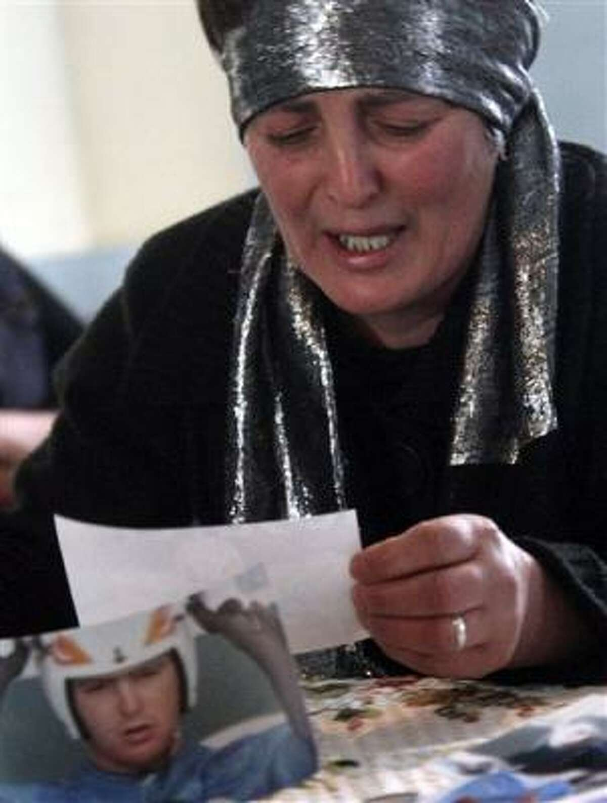 Dodo Kharazishvili, mother of late Georgian olympic luger Nodar Kumaritashvili, cries while looking at photos of her son at their home in the town of Bakuriani, a top ski resort in the Caucasus Mountains.