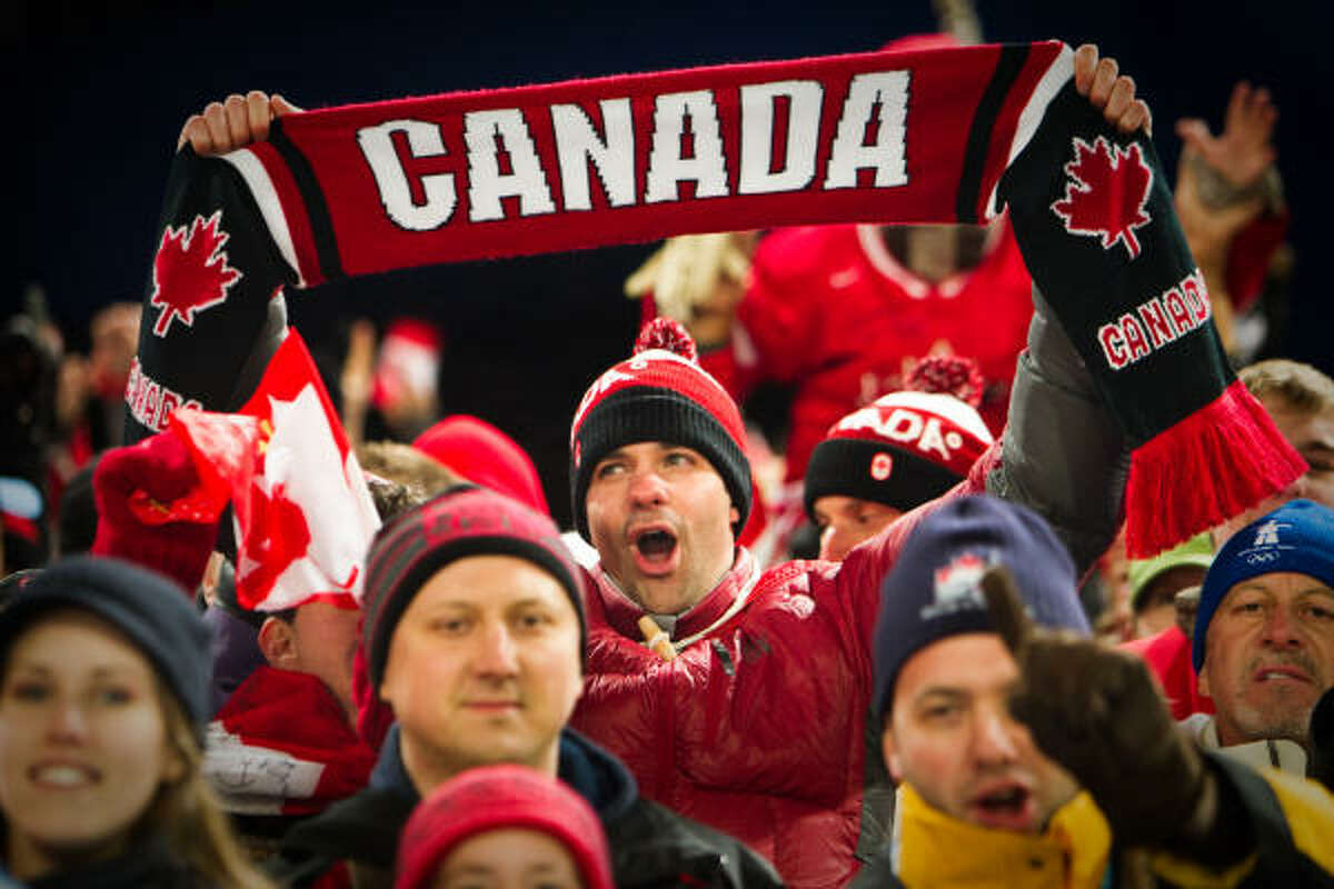 Fans celebrate the victory by Alexandre Bilodeau of Canada in the men's moguls finals. With a gold medal performance in the event, Bilodeau earned his country their first Olympic victory on home soil.