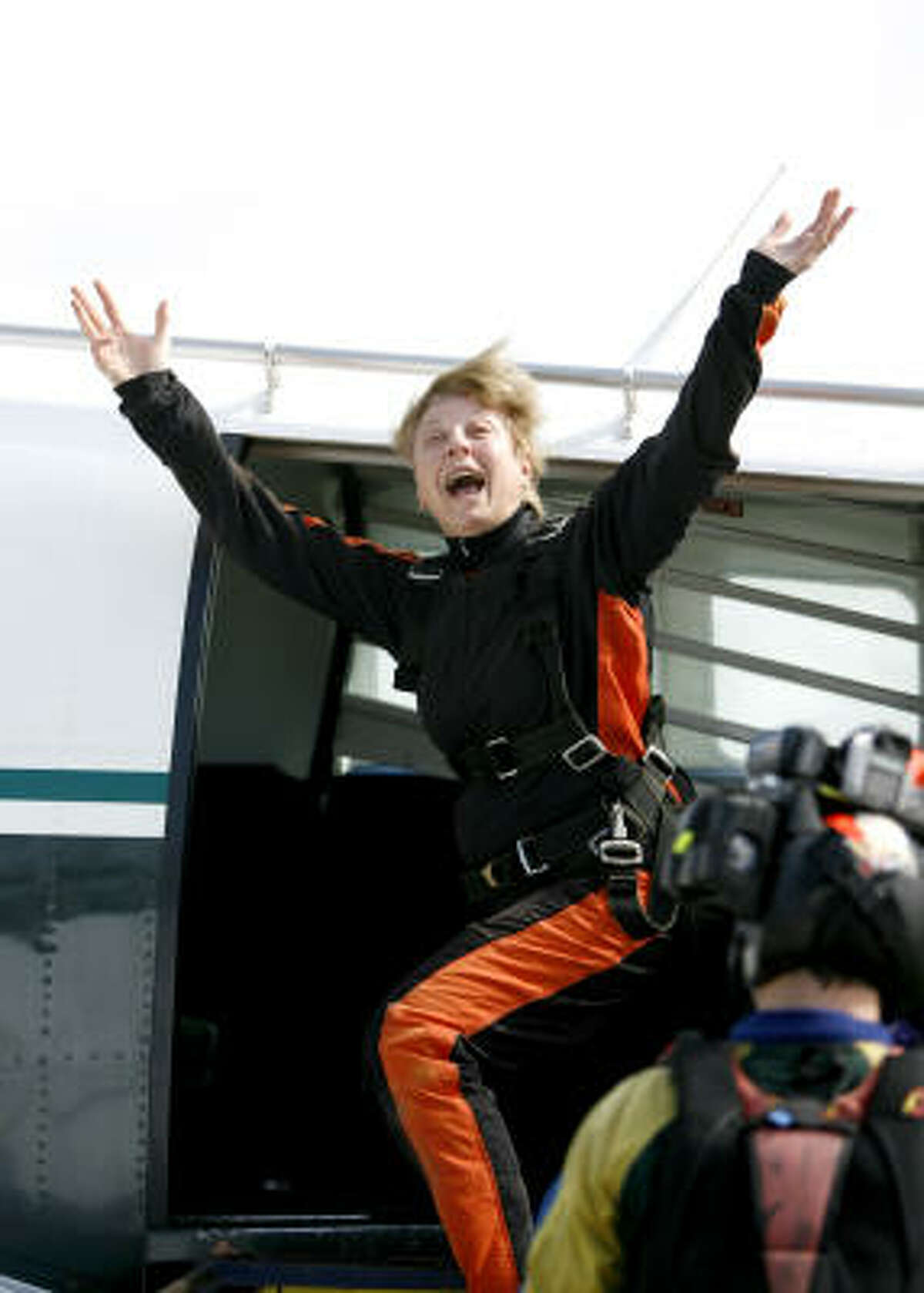 Sister Jane Meyer, 71, blows a kiss to all of her students, teachers and supporters as she boards an airplane to skydive.