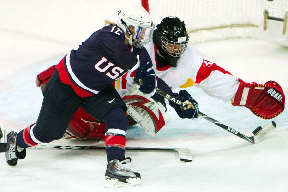 Team USA forward Jenny Potter slips the puck past China goalie Yao Shi on her way to a hat trick.