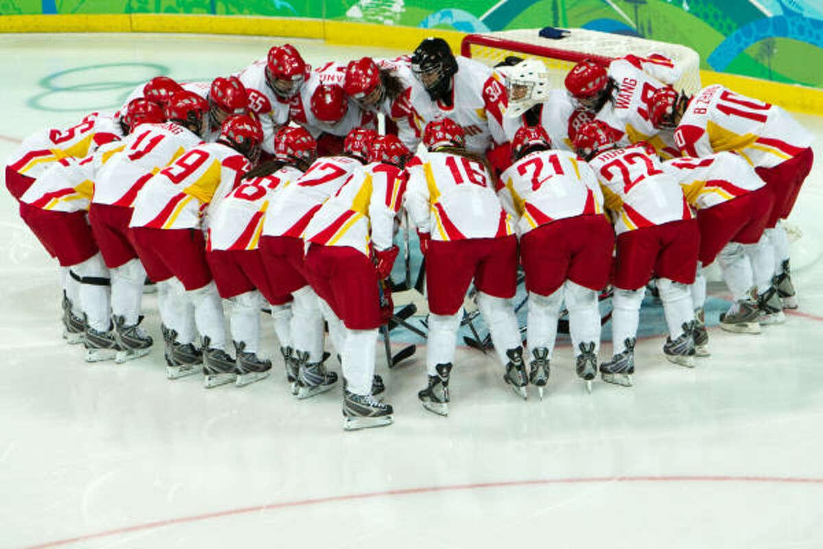 Team China huddles around goalie Yao Shi before the Group B opener.