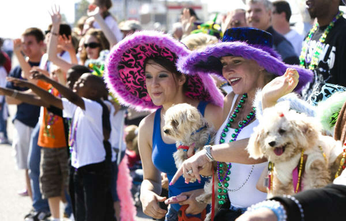Faith Nez, left, and Connie Travis watch the Krewe of Barkus and Meoux Mardi Gras parade.