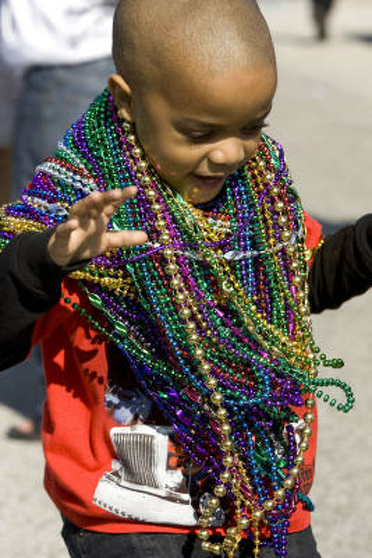 Darron Derouselle, 5, is loaded down with beads as he watches the Childrens' Mardi Gras parade.