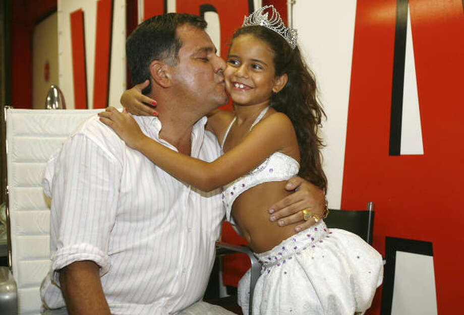 Viradouro samba school drum queen Julia Lira is kissed by her father, Marcos Lira, the samba school president, in Rio de Janeiro on Feb. 10, 2010, after a court gave permission to the 7-year-old girl to lead a parade in the city's upcoming famed Carnival, despite protests from child rights groups. Read the story | More world news | Chron.com Photo: CARLOS MORAES, AFP/Getty Images
