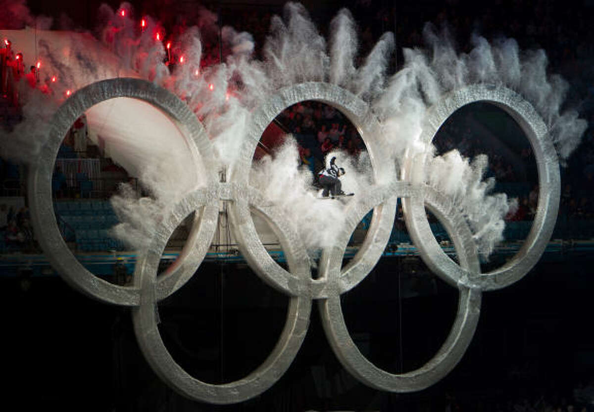 A snowboarder flies through the Olympic rings.