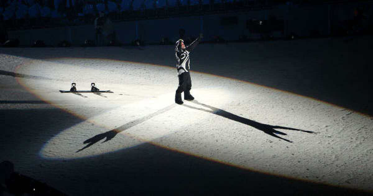 Snowboarder Johnny Lyall reacts after making his landing following a leap through the Olympic rings.