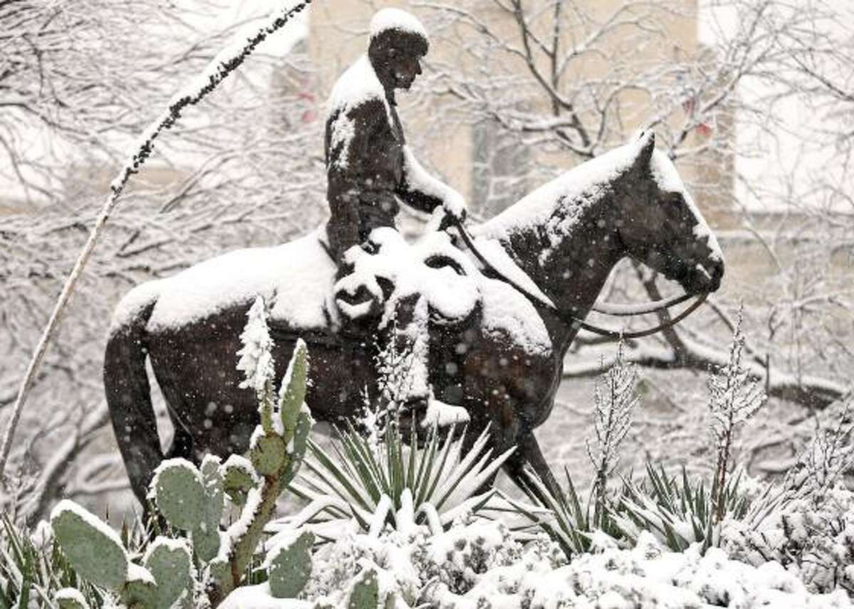 Snow covers a statue of Will Rogers in Fort Worth.