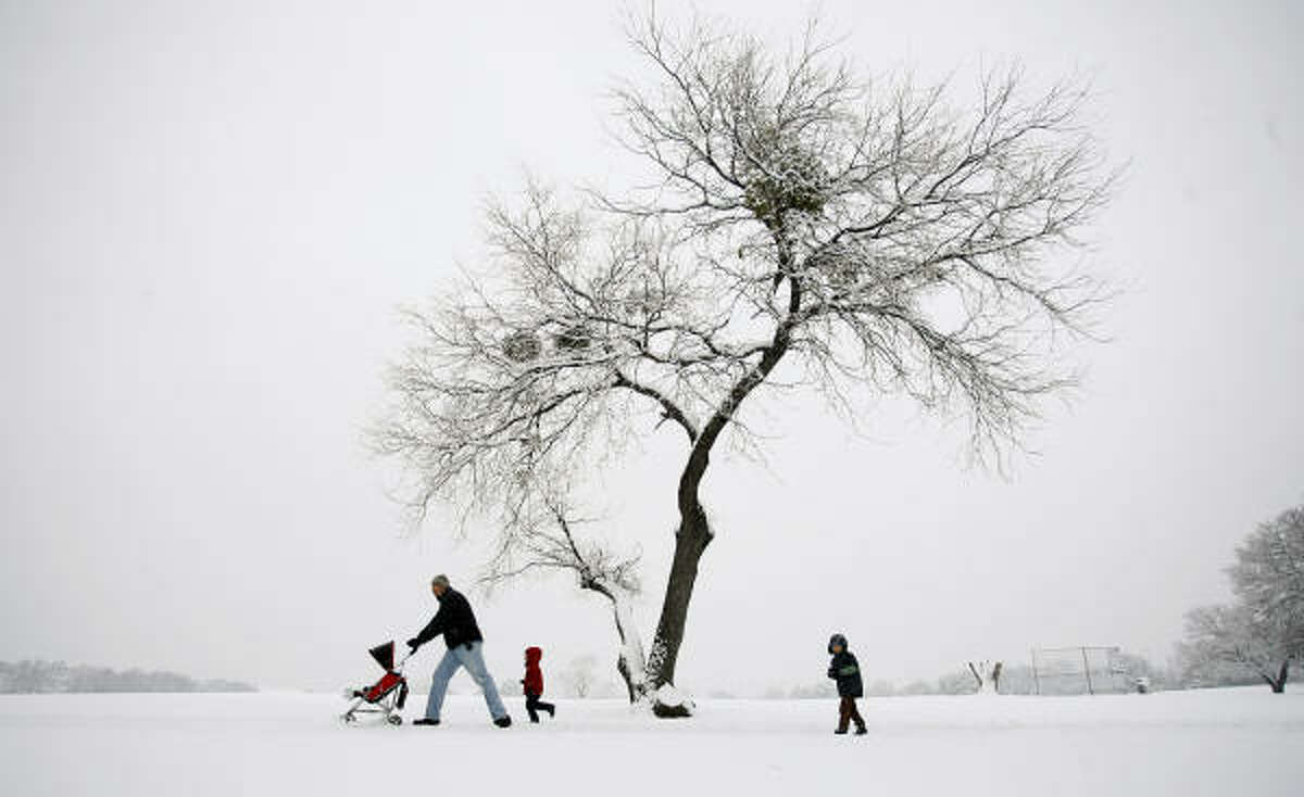 Jared Orr walks in the snow with his children, from left, 9 month-old Jude, Daniel, 4, and Abraham, 5, in Veterans Park in Arlington, Texas.