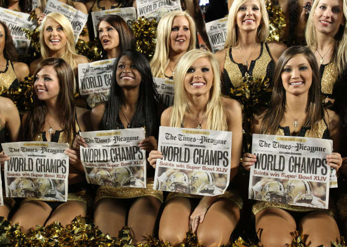 New Orleans Saints cheerleaders hold papers celebrating the Saints' win over the Indianapolis Colts in Super Bowl XLIV on Feb. 7, 2010.