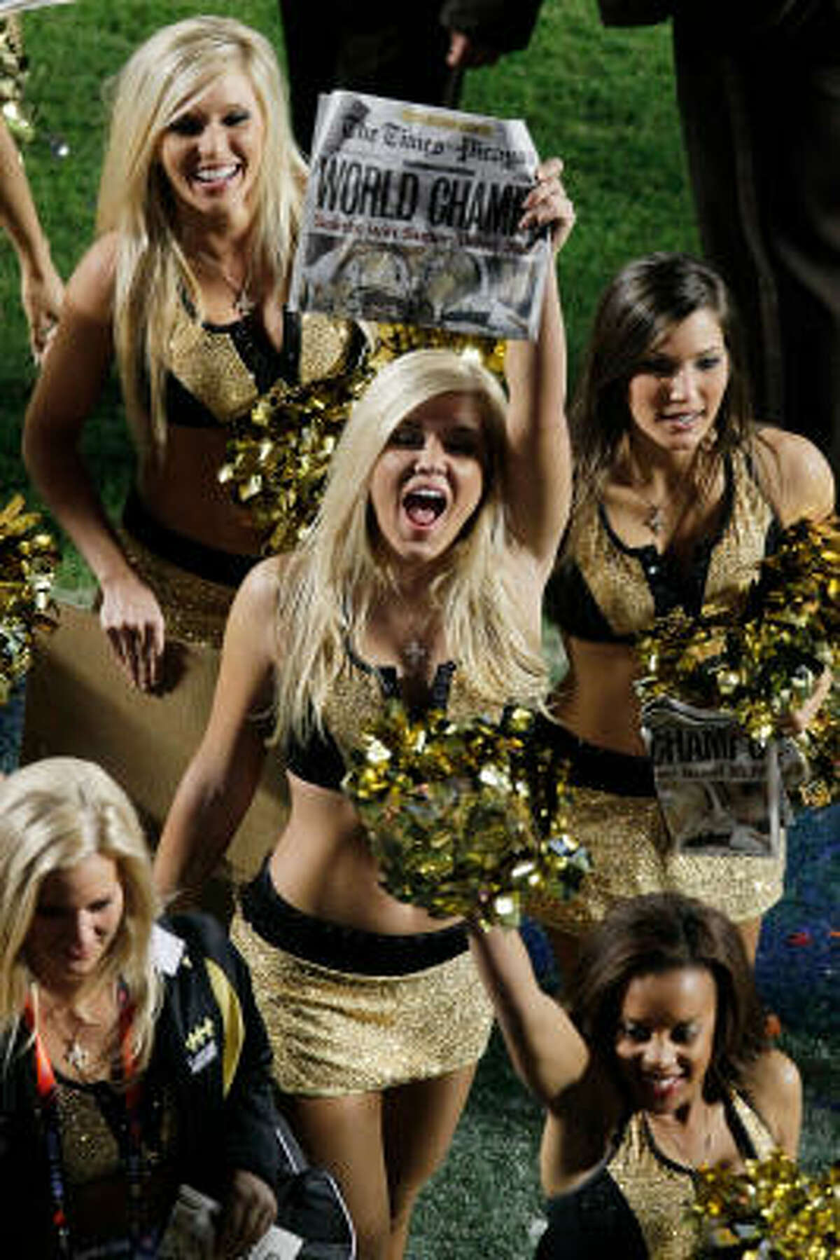 New Orleans Saints cheerleaders hold new papers celebrating the Saints' win over the Indianapolis Colts.