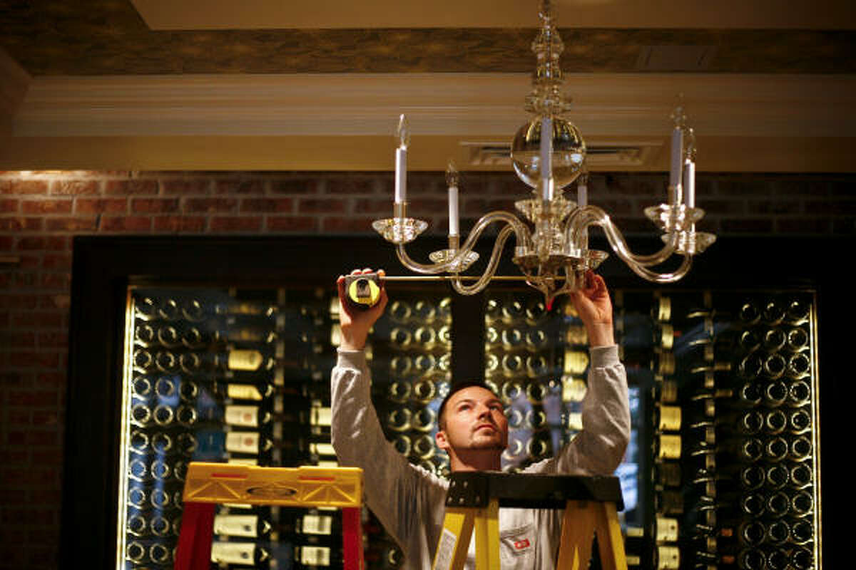 Will Messenger works to install a chandelier at Brennan's restaurant.