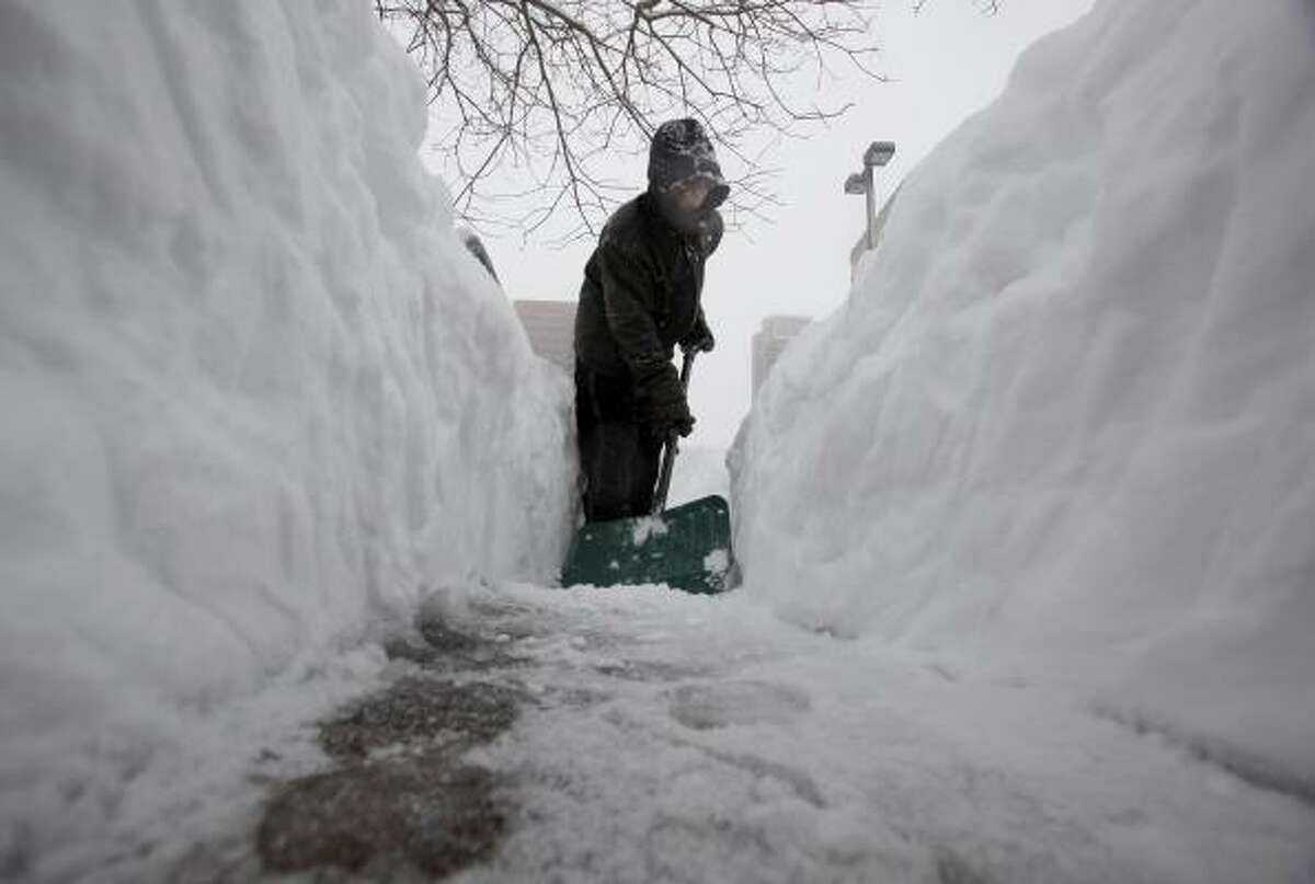 Johnny Kim shovels a sidewalk at the Inner Harbor during a winter storm in Baltimore.