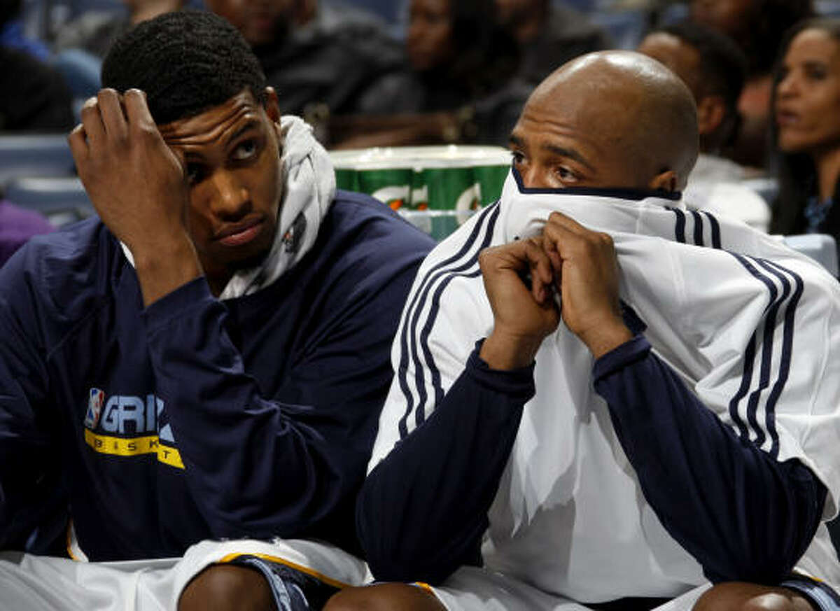 Grizzlies forward Rudy Gay, left, and guard Jamaal Tinsley watch during the second half of the 18-point loss to the visiting Rockets.
