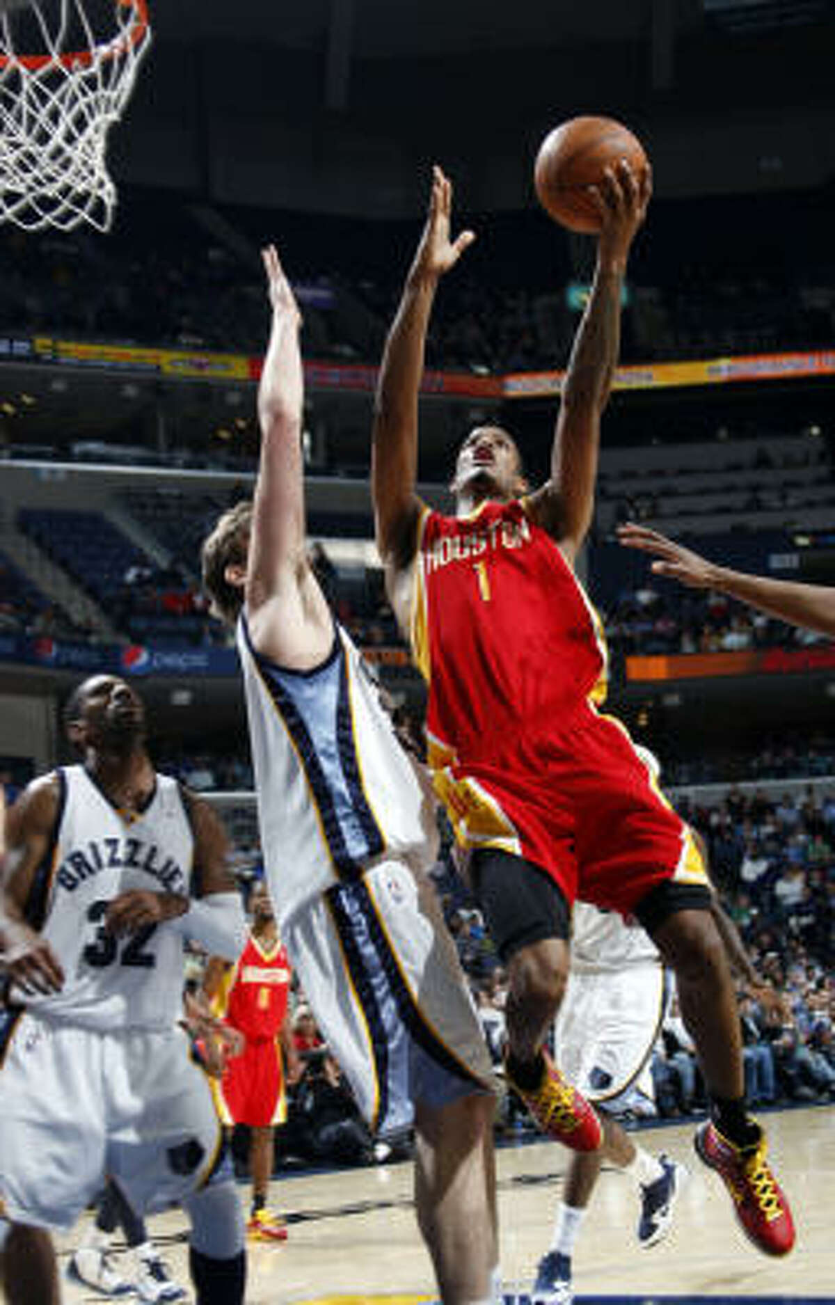 Rockets guard Trevor Ariza shoots over Grizzlies center Marc Gasol as guard O.J. Mayo watches.
