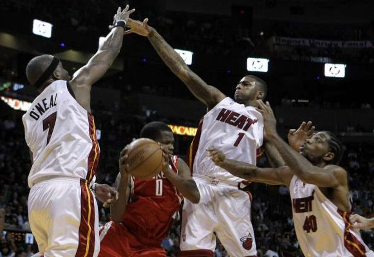 Rockets guard Aaron Brooks tries to pass the ball as a trio of Heat defenders converge on him.