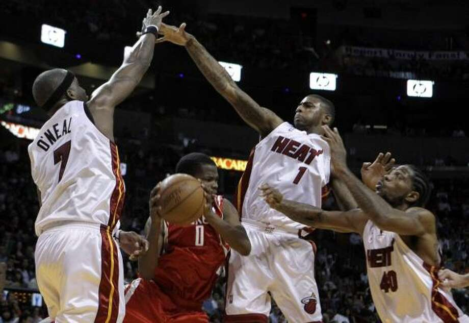 Rockets guard Aaron Brooks tries to pass the ball as a trio of Heat defenders converge on him. Photo: Lynne Sladky, AP