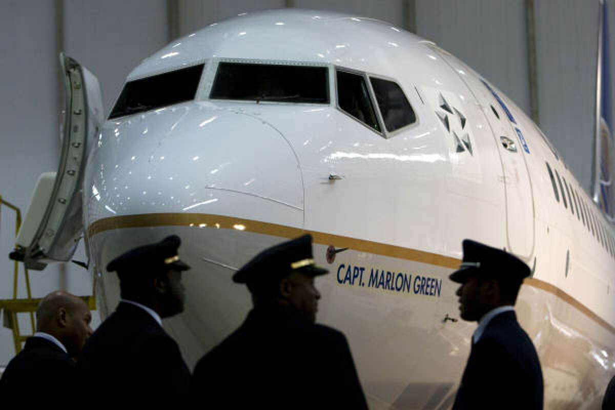 Pilots Matthew Caldwell, Ian Howe and Paschal Alexander talk in front of a Continental 737 named after Capt. Marlon Green, the first African American commercial pilot, at Continental's Hanger E at Bush Intercontinental Airport in Houston. After nine years and more than 3,000 hours of flight time of flying multi-engine planes in the Air Force in the 1950s, Capt. Green was rejected by every commercial airline when he applied for jobs as a pilot because of the color of his skin. Green won a landmark legal battle where he was later hired by Continental Airlines. Green died last year at the age of 80 in Denver, Colo.