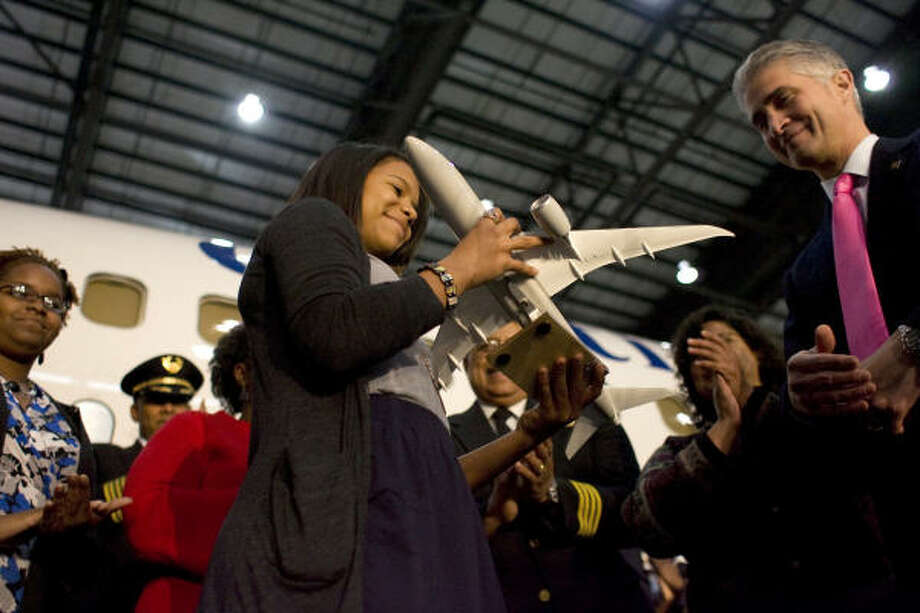 The granddaughter of Capt. Marlon Green, the first African American commercial pilot, Kanza El Hamel, 15, is given a replica airplane from Continental Airlines President and CEO Jeff Smisek, after a press conference announcing Continental named a 737 aircraft after him. Photo: Johnny Hanson, Chronicle