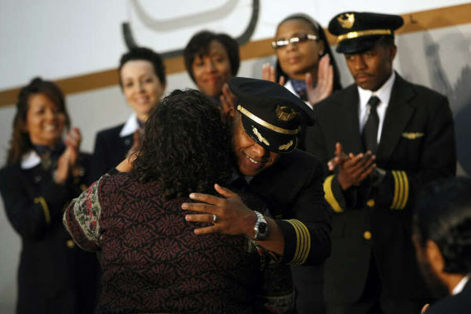 Ray-Sean Silvera, hugs Monica Green, the daughter of Capt. Marlon Green, the first African American commercial pilot, during a ceremony naming a 737 after Green. Silvera advocated something be done to honor Green after his death last year. Photo: Johnny Hanson, Chronicle