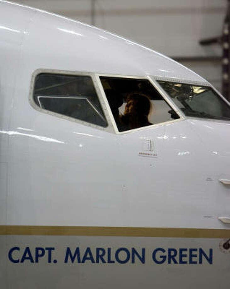 The granddaughter of Capt. Marlon Green, the first African American commercial pilot, Malaika El Hamel, 19, sits in the cockpit of a Continental 737 aircraft named after him. Photo: Johnny Hanson, Chronicle