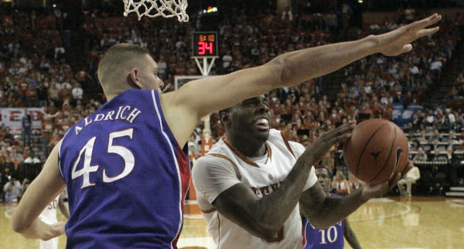 Texas forward Damion James, right, is guarded by Cole Aldrich. James and J'Covan Brown combined for 52 points, but the rest of the Longhorns scored just 16 on 5-for-27 shooting. Photo: Harry Cabluck, AP