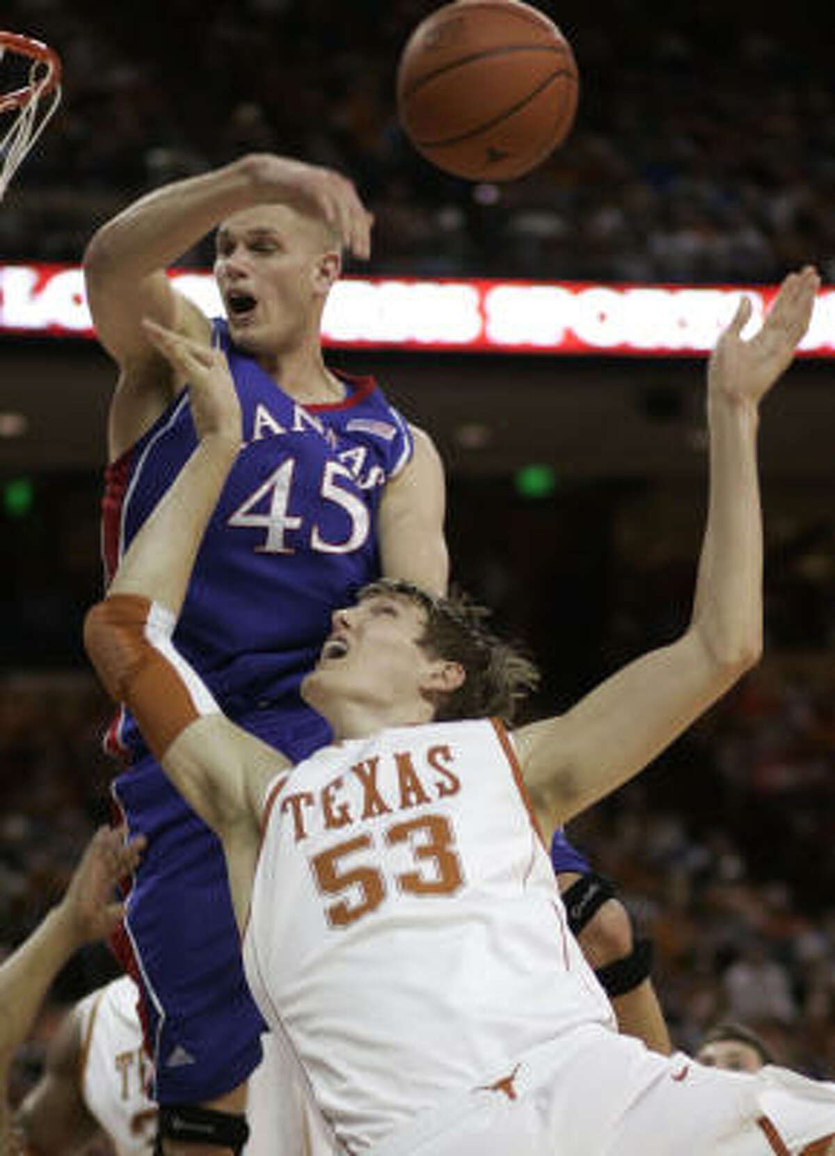 Kansas center Cole Aldrich turns away the shot of Texas' Clint Champman for one of his six blocks.