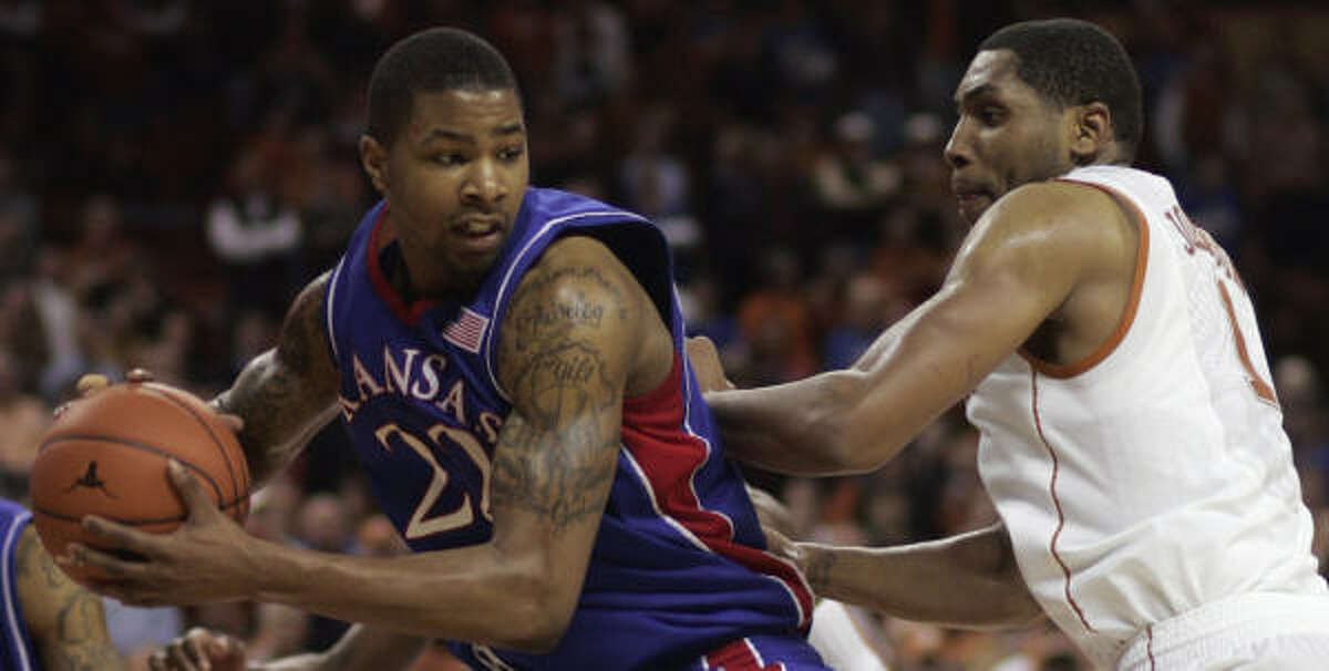 Kansas forward Marcus Morris, left, is guarded by Texas forward Gary Johnson. Morris led the Jayhawks with 18 points.
