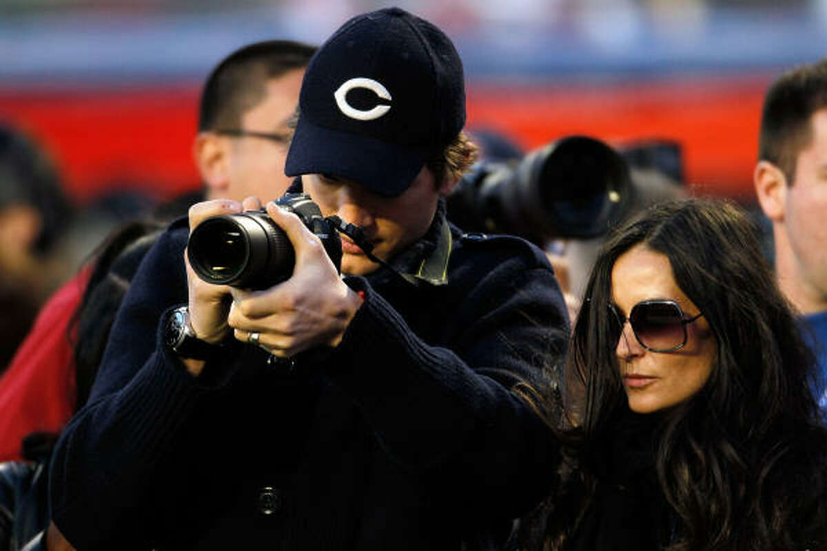 Actor Ashton Kutcher takes pictures from the sidelines with actress Demi Moore prior to Super Bowl XLIV.