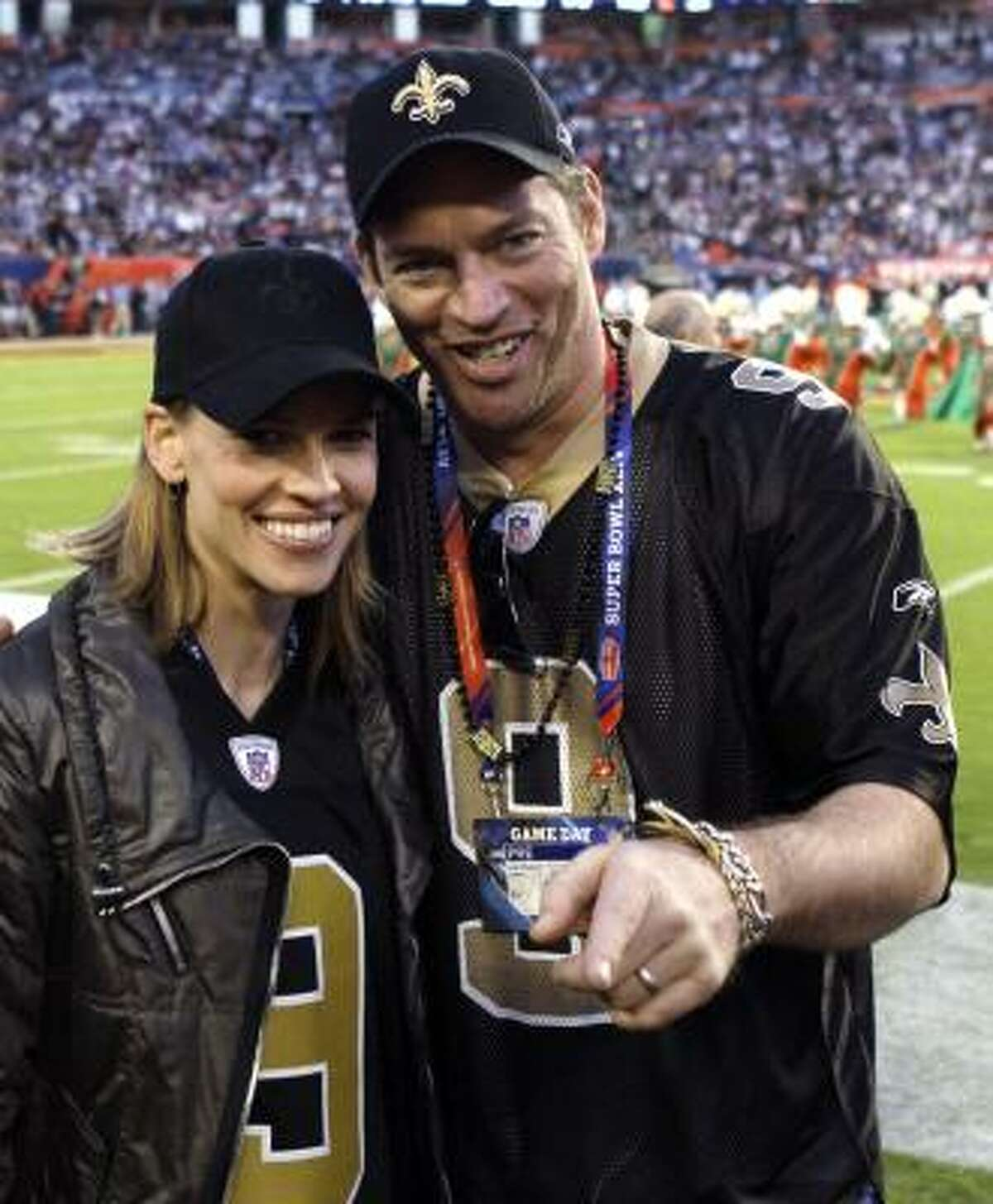 Actress Hilary Swank and singer Harry Connick Jr., are seen on the field before Super Bowl XLIV .