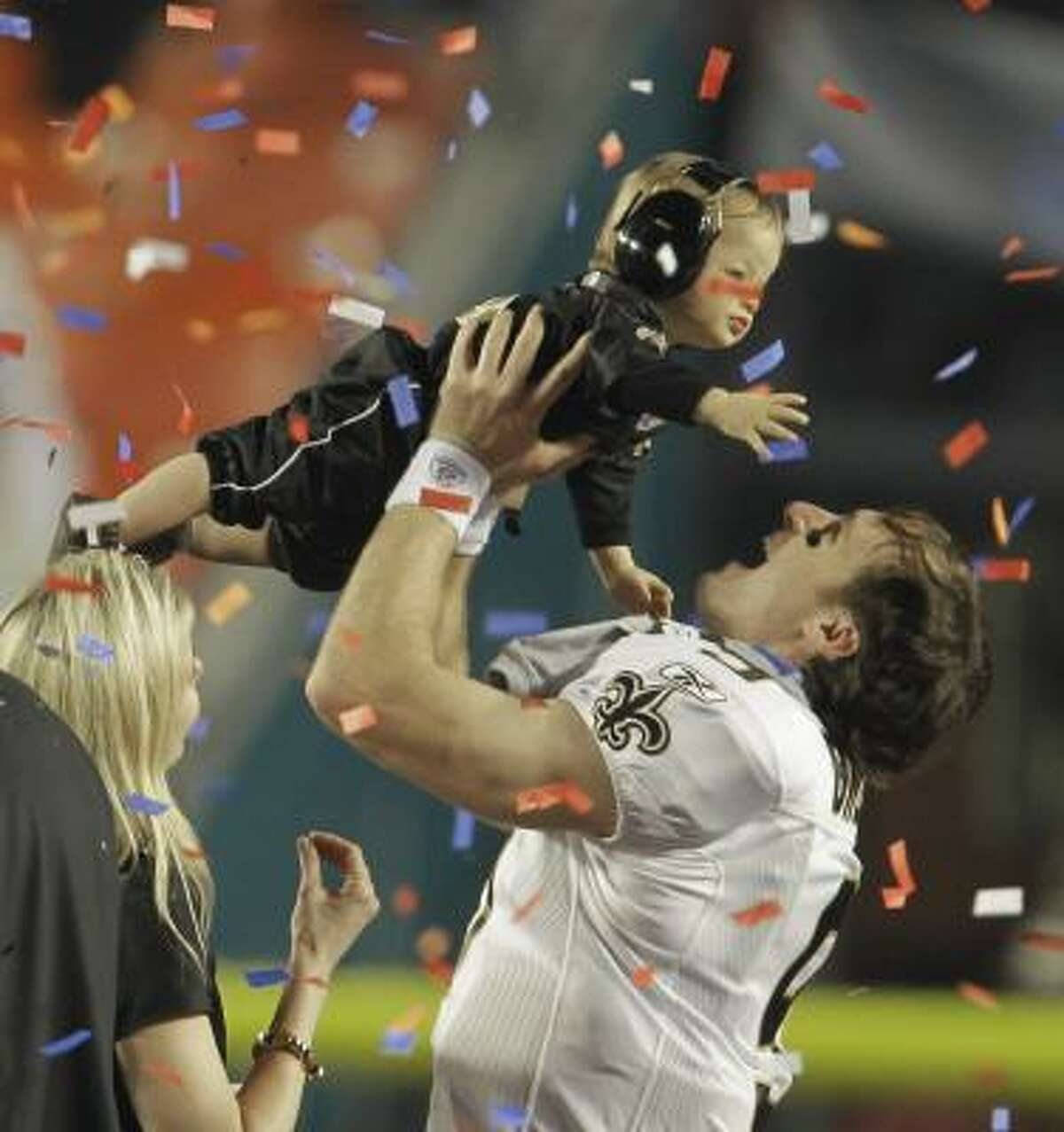 Saints quarterback Drew Brees holds his son during the victory celebration.