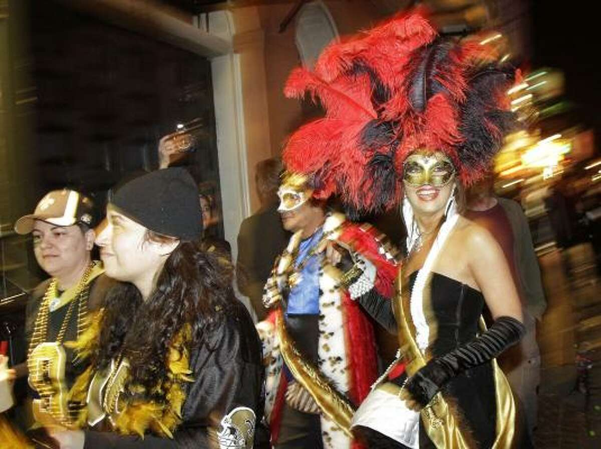Saints fans and people dressed for Mardi Gras take to the streets to celebrate.