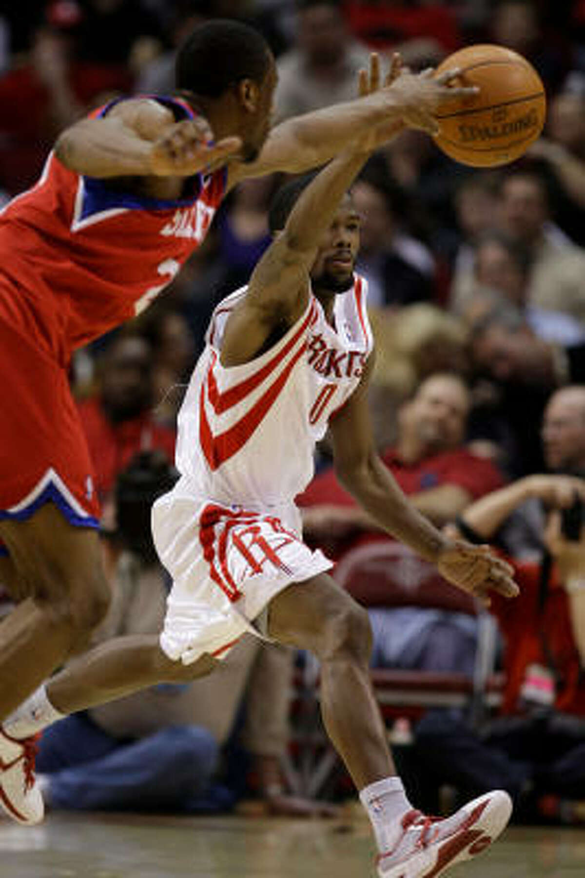 Philadelphia 76ers forward Thaddeus Young, left, and Rockets guard Aaron Brooks chase a loose ball during Saturday's game at Toyota Center. Brooks scored a game-high 34 points, but the Rockets lost 102-95.