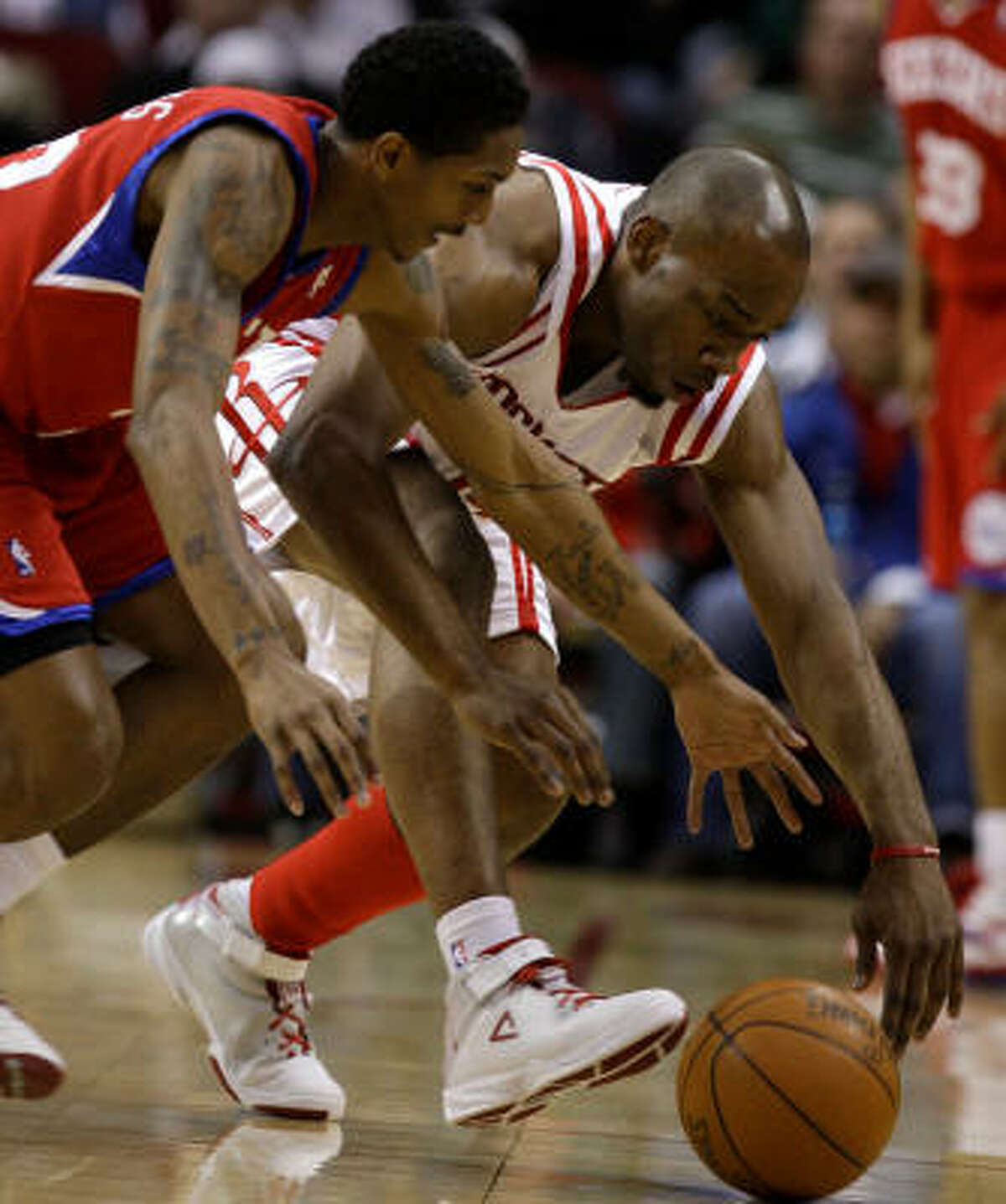 Philadelphia's Louis Williams, left, and Rockets forward Carl Landry battle for a loose ball.