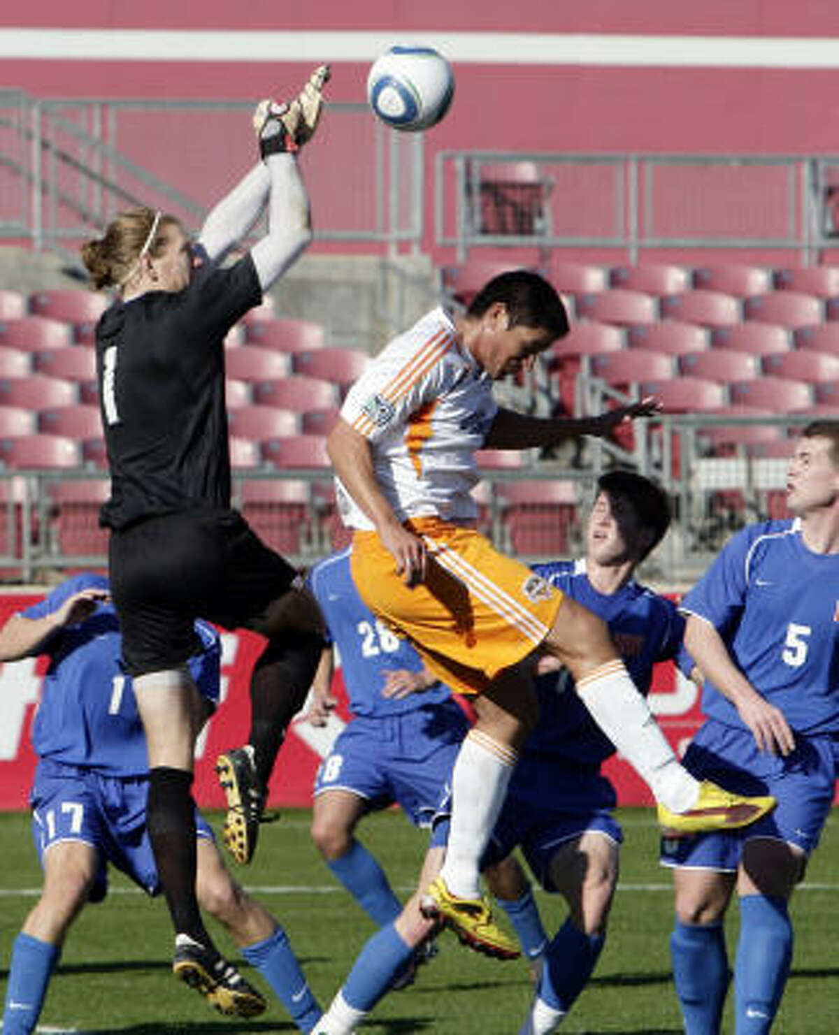 HBU goalkeeper Chris Dodd punches the ball away before the Dynamo's Brian Ching can get a head on it.