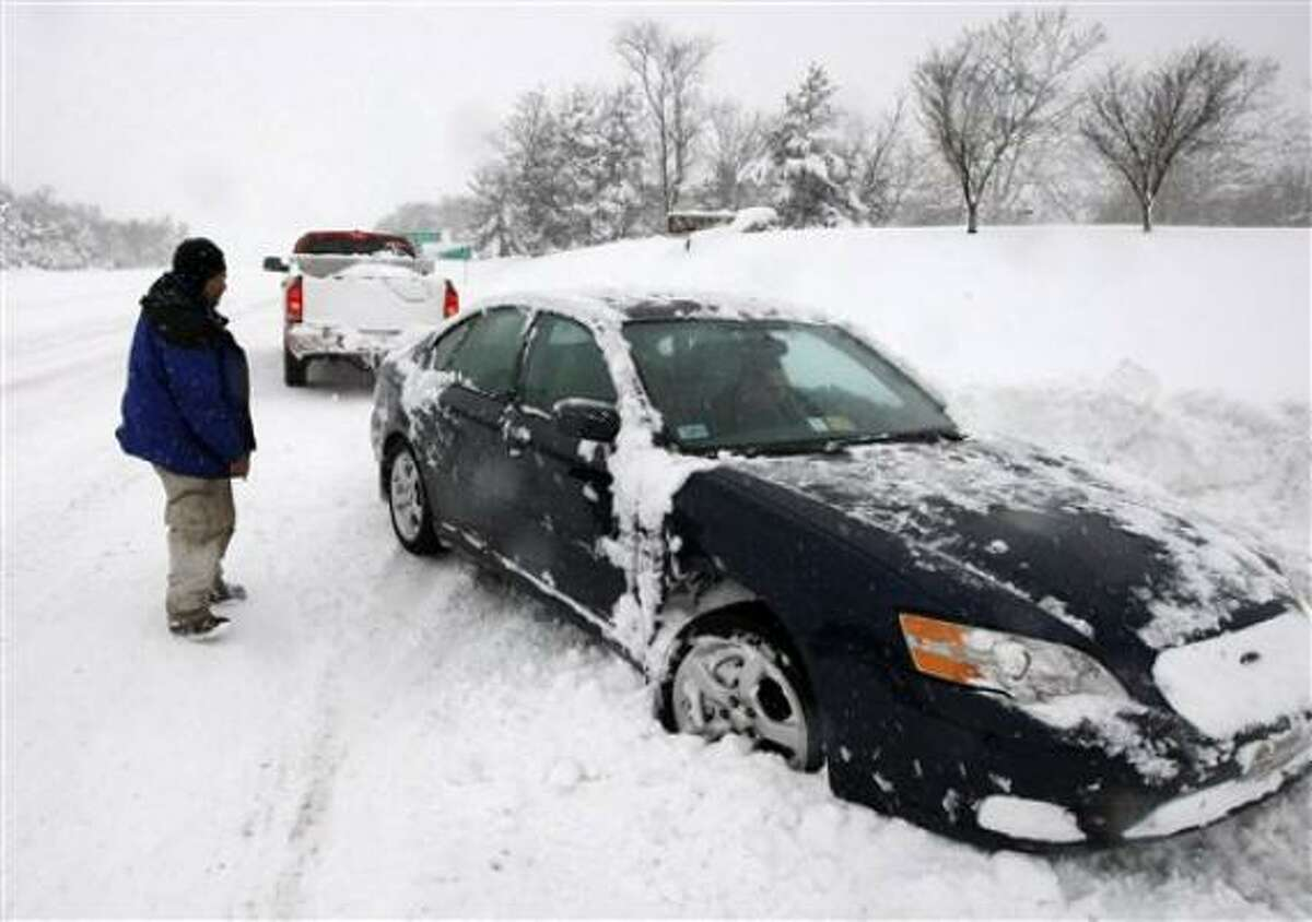 Rich Cavey shovels snow away from his car in front of his home during a winter storm in Catonsville, Md. on Saturday.