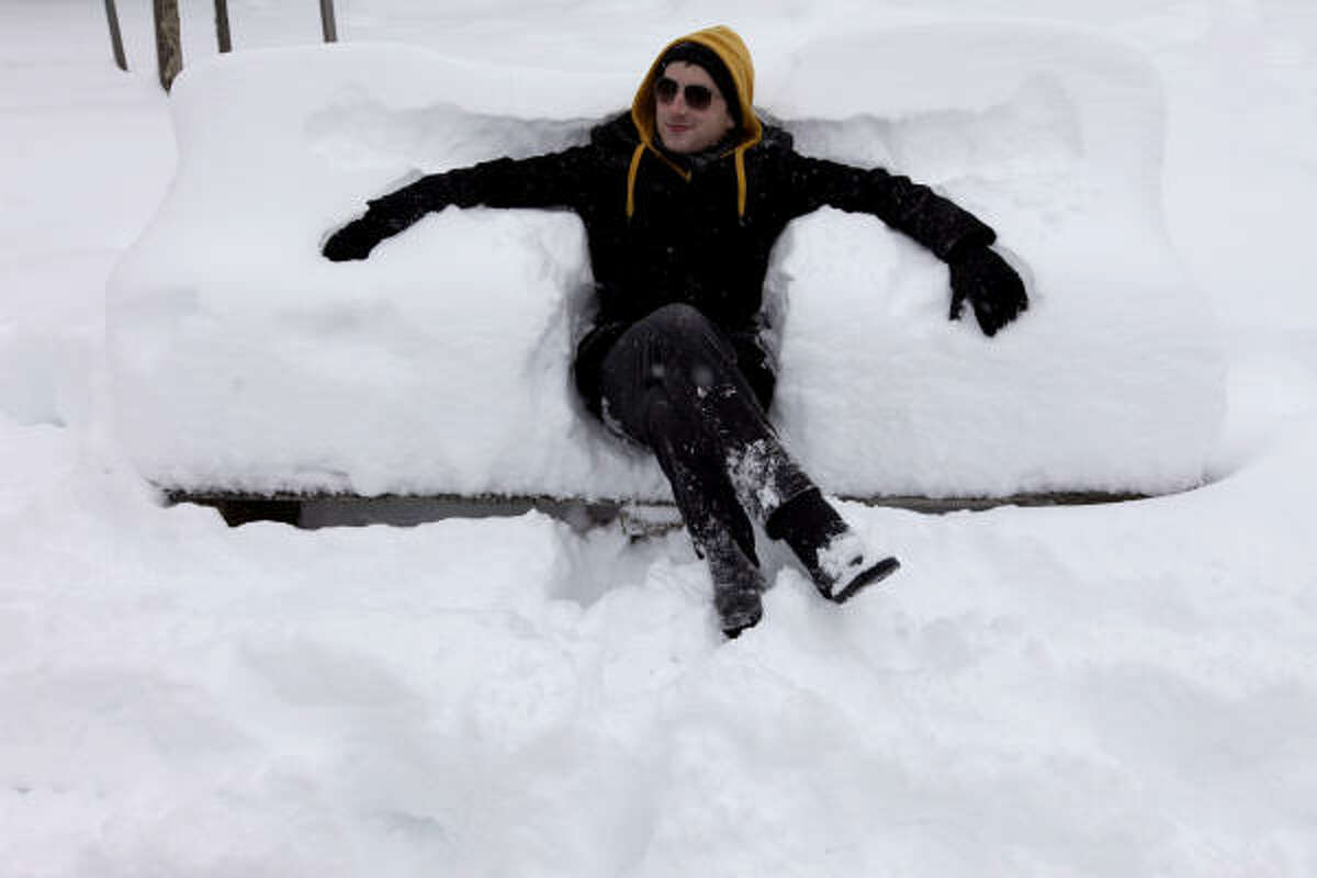 Rene Maes sits on a snow covered bench seat at Meridian Hill Park Washington on Saturday.