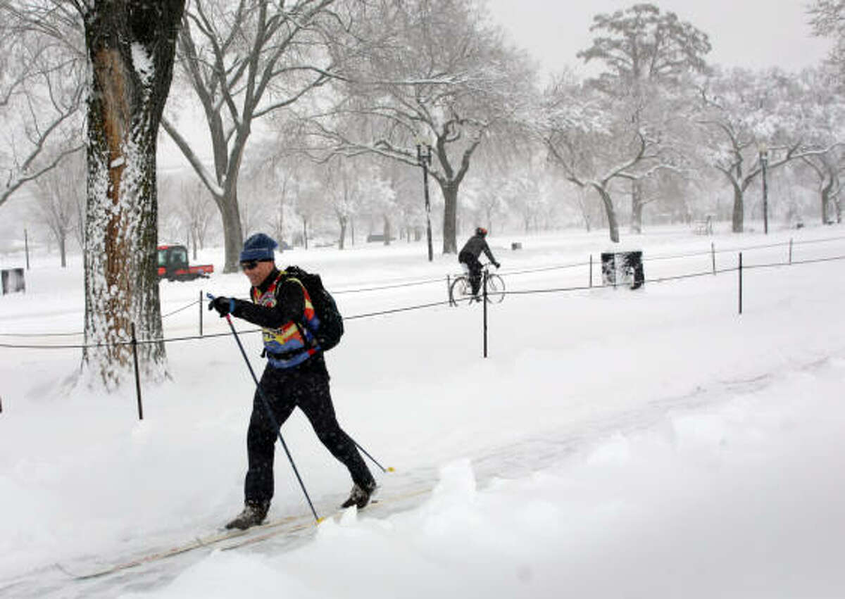 A skier and a bicyclist find different ways to move about Washington during a winter snowstorm that buried the city Saturday under what could be record-breaking snowfall.