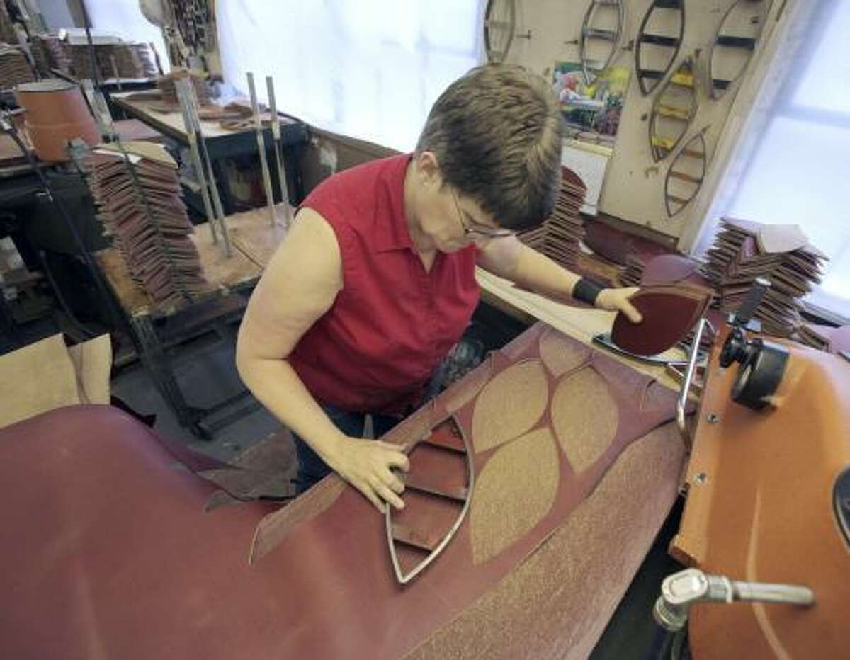 Michelle Burkett cuts a sheet of leather into four panels to make the official Super Bowl XLIV football at the Wilson Sporting Goods factory in Ada, Ohio. The factory began making the game balls Jan. 25, the day after the conclusion of the NFC and AFC championship games. Wilson has been the official football supplier for the NFL since 1941.