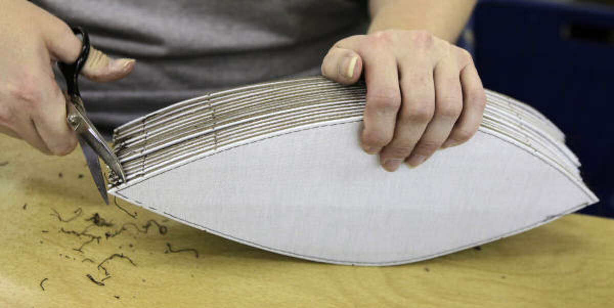 Melissa Putman snips threads from the stitched lining of panels to be made into the official balls for Super Bowl XLIV.