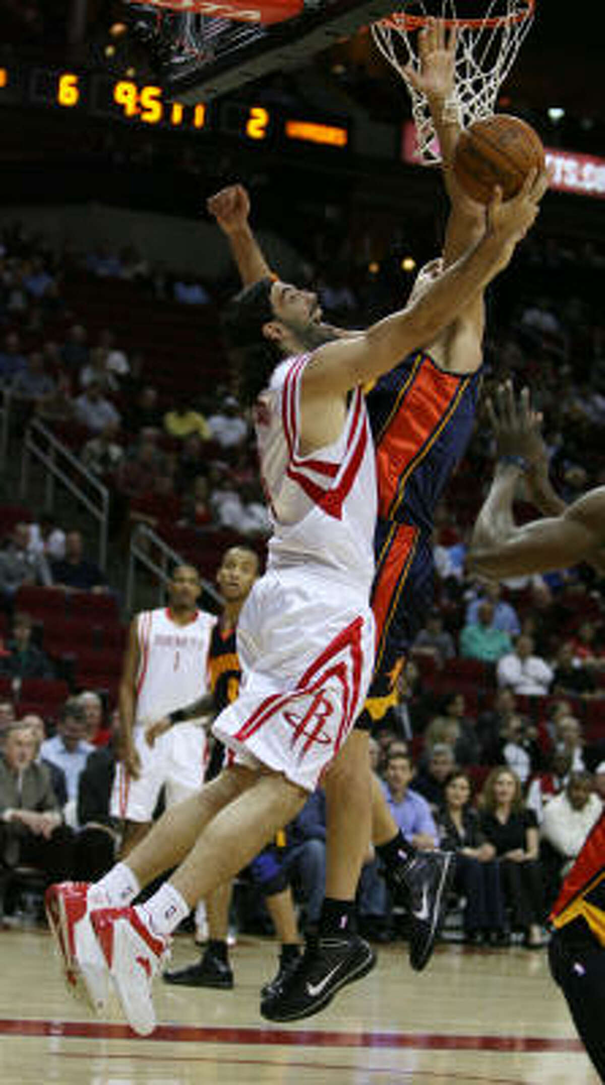 Rockets forward Luis Scola goes up for a reverse layup while Warriors center Andris Biedrins attempts to defend.