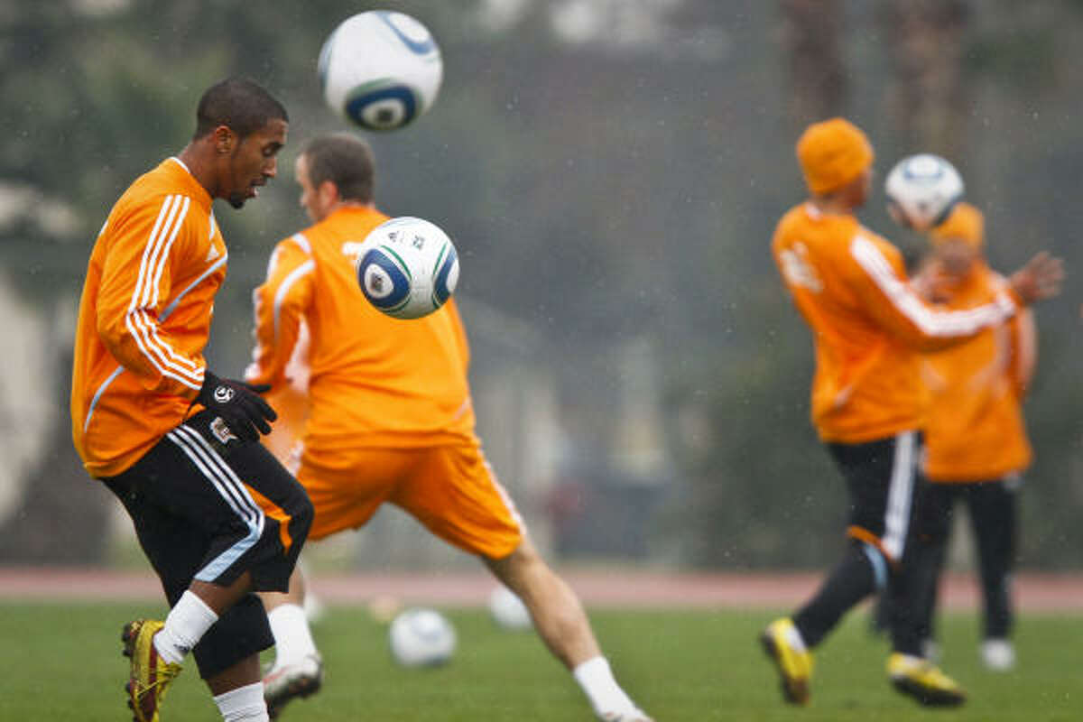 The Dynamo's Corey Ashe, left, gets his touches during warmup drills for the first practice of the season.