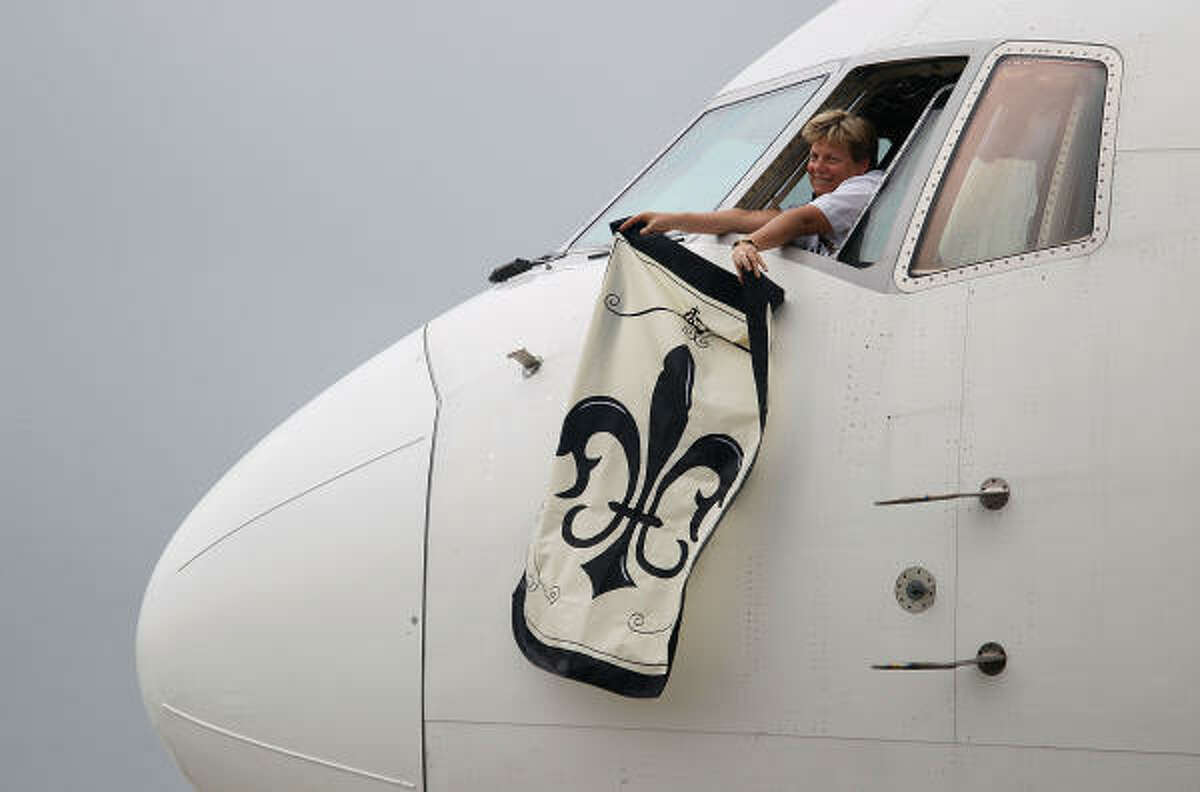A Delta Airlines pilot waves a Saints flag after landing with members of the New Orleans Saints at Miami International Airport.