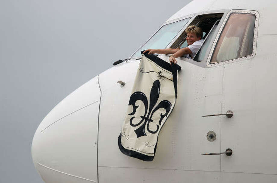 A Delta Airlines pilot waves a Saints flag after landing with members of the New Orleans Saints at Miami International Airport. Photo: Scott Halleran, Getty Images
