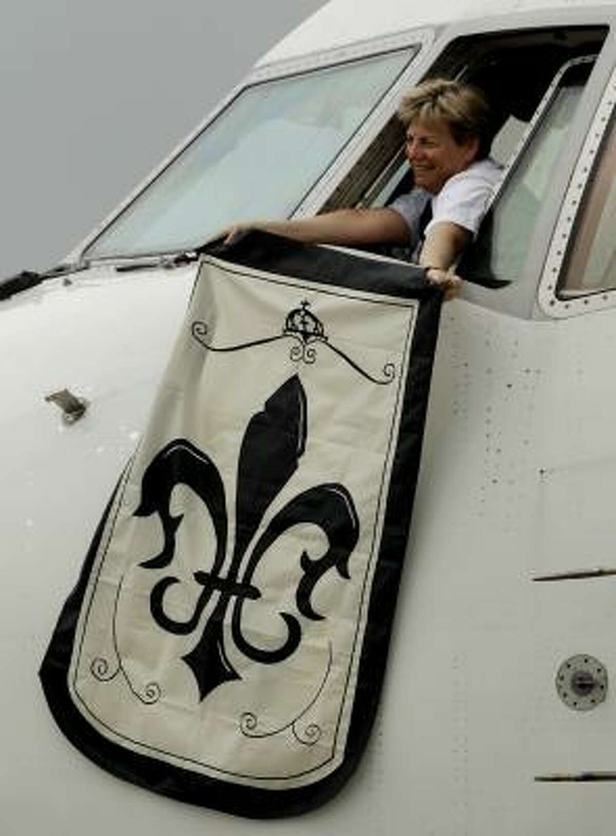 A New Orleans Saints flag is waved out the window of the plane as the team arrives in Miami.