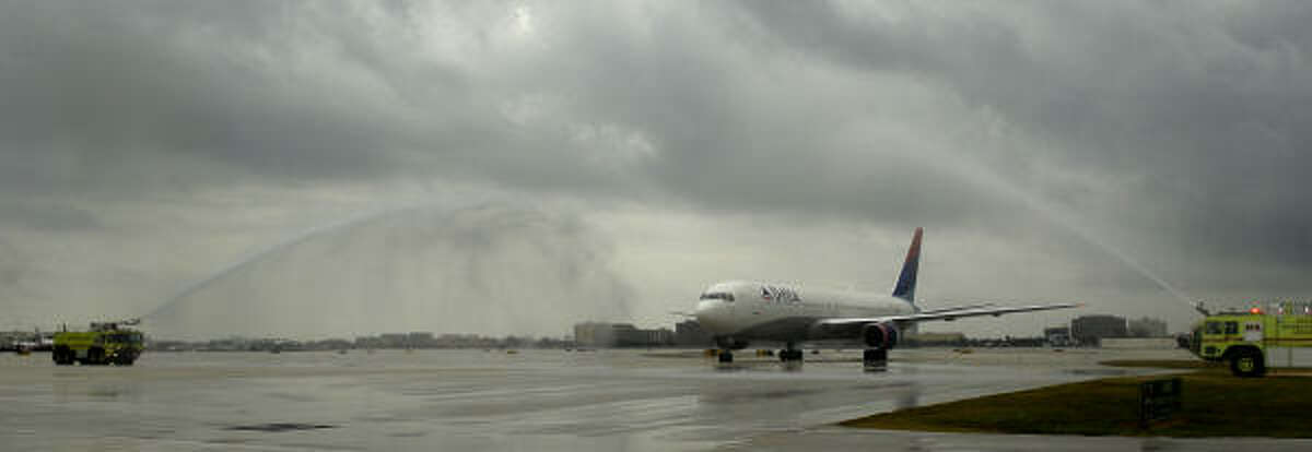 A jet carrying players players for the New Orleans Saints taxies under water cannons as the team arrives in Miami.